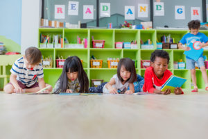 Group of diversity kid lay down on floor and reading tale book